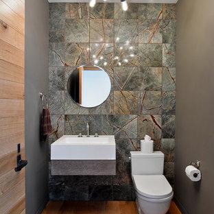 Cette image montre un WC et toilettes design avec un lavabo suspendu, un WC à poser, un mur gris, un sol en bois brun, du carrelage en marbre et un carrelage gris.
