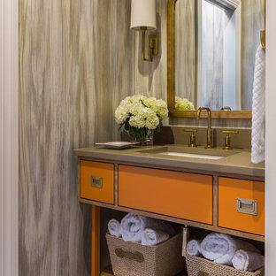 Exemple d'un WC et toilettes chic de taille moyenne avec un lavabo encastré, des portes de placard oranges, un carrelage beige, un sol en marbre et un plan de toilette marron.