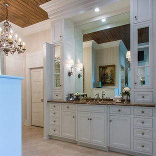 Idées déco pour un très grand WC et toilettes éclectique avec des portes de placard blanches, un sol en carrelage de porcelaine, un lavabo encastré, un plan de toilette en marbre, un placard avec porte à panneau encastré, des carreaux de porcelaine, un mur blanc et un sol beige.