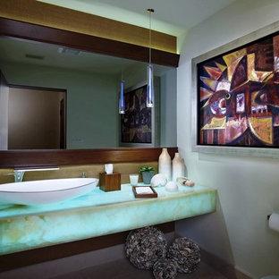 Cette photo montre un grand WC et toilettes tendance avec un placard sans porte, un mur blanc, un sol en calcaire, une vasque, un plan de toilette en onyx, un WC à poser, un carrelage blanc, un sol beige et un plan de toilette turquoise.