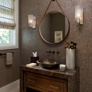 ダラスの中くらいのコンテンポラリースタイルのおしゃれなトイレ・洗面所 (ベッセル式洗面器、家具調キャビネット、茶色いタイル、モザイクタイル、御影石の洗面台、トラバーチンの床、濃色木目調キャビネット、ブラウンの洗面カウンター) の写真