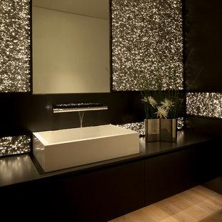 На фото: туалет в современном стиле с настольной раковиной, черной плиткой и черной столешницей с