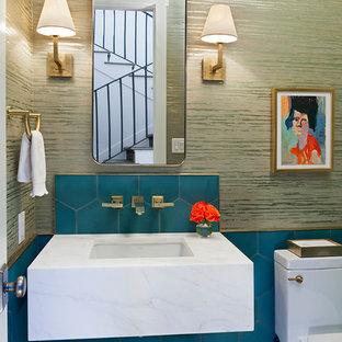 На фото: туалеты в стиле современная классика с унитазом-моноблоком, синей плиткой, бежевыми стенами, паркетным полом среднего тона, врезной раковиной, коричневым полом и белой столешницей