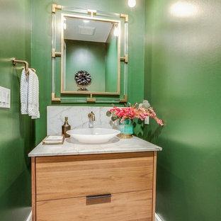 На фото: с высоким бюджетом маленькие туалеты в стиле модернизм с плоскими фасадами, светлыми деревянными фасадами, унитазом-моноблоком, зеленой плиткой, зелеными стенами, полом из цементной плитки, раковиной с пьедесталом, столешницей из кварцита, черным полом, бежевой столешницей и плиткой из листового камня