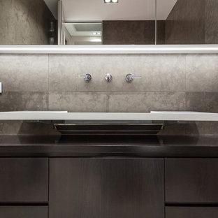 Ispirazione per un piccolo bagno di servizio moderno con ante lisce, ante grigie, piastrelle grigie, piastrelle in travertino, pareti grigie, pavimento in travertino, lavabo sospeso, top in marmo, pavimento grigio e top grigio