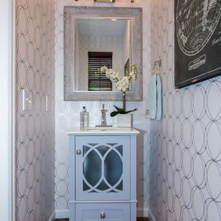 Photo of a small farmhouse cloakroom in Denver with glass-front cabinets, blue cabinets, white walls, medium hardwood flooring, a submerged sink, solid surface worktops and brown floors.