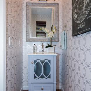 Cette photo montre un petit WC et toilettes nature avec un placard à porte vitrée, des portes de placard bleues, un mur blanc, un sol en bois brun, un lavabo encastré, un plan de toilette en surface solide et un sol marron.