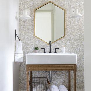 На фото: туалеты среднего размера в стиле кантри с открытыми фасадами, полом из цементной плитки, фасадами цвета дерева среднего тона, бежевыми стенами, консольной раковиной и серым полом