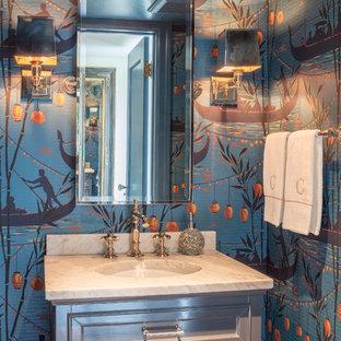 Inspiration pour un WC et toilettes traditionnel avec un placard avec porte à panneau encastré, des portes de placard grises, un mur multicolore, un lavabo encastré et un plan de toilette blanc.