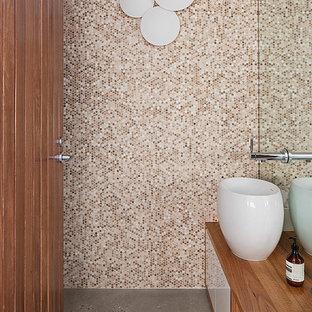 На фото: туалет в современном стиле с настольной раковиной, плоскими фасадами, фасадами цвета дерева среднего тона, столешницей из дерева, бежевой плиткой, плиткой мозаикой, бетонным полом и коричневой столешницей с