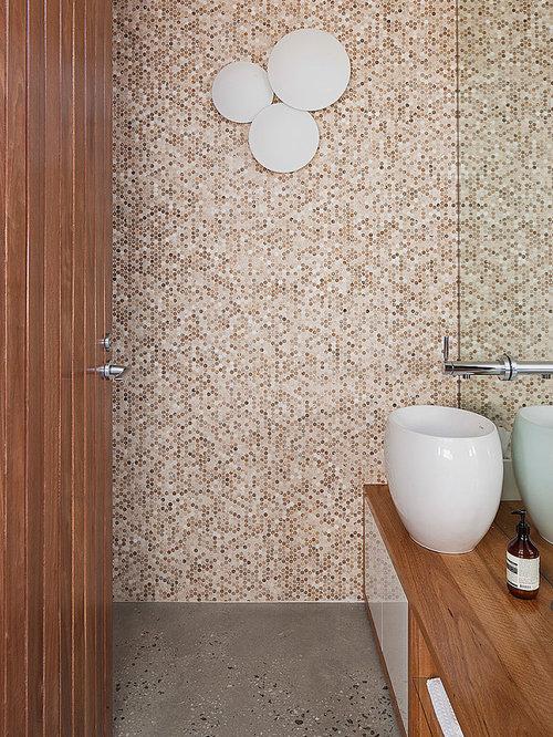 inspiration for a beige tile and mosaic tile concrete floor powder room remodel in melbourne