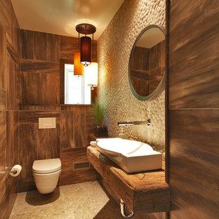 ニューヨークの小さいラスティックスタイルのおしゃれなトイレ・洗面所 (木製洗面台、壁掛け式トイレ、ベージュのタイル、石タイル、横長型シンク、ブラウンの洗面カウンター) の写真