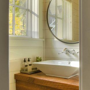 Foto på ett litet vintage toalett, med öppna hyllor, skåp i mellenmörkt trä, vita väggar, ett fristående handfat och träbänkskiva