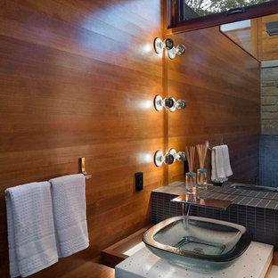 シーダーラピッズのラスティックスタイルのおしゃれなトイレ・洗面所 (ベッセル式洗面器、フラットパネル扉のキャビネット、中間色木目調キャビネット、グレーのタイル、モザイクタイル、スレートの床、再生グラスカウンター) の写真