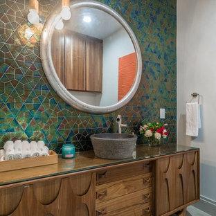Idées déco pour un WC et toilettes classique avec un placard en trompe-l'oeil, des portes de placard en bois brun, un carrelage multicolore, un mur blanc, une vasque et un plan de toilette en verre.