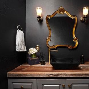 トロントの小さいトランジショナルスタイルのおしゃれなトイレ・洗面所 (ベッセル式洗面器、レイズドパネル扉のキャビネット、グレーのキャビネット、木製洗面台、黒い壁、ブラウンの洗面カウンター) の写真