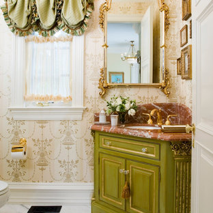 Powder room - traditional powder room idea in New York with an undermount sink, raised-panel cabinets, green cabinets, beige walls and brown countertops