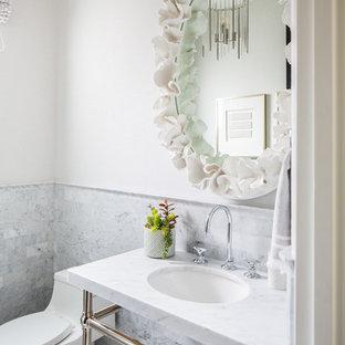 На фото: туалет в средиземноморском стиле с мраморной плиткой, белыми стенами, полом из мозаичной плитки, раковиной с несколькими смесителями и мраморной столешницей