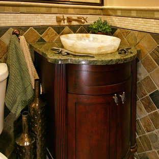 Photo of a small classic cloakroom in Minneapolis with a vessel sink, dark wood cabinets, granite worktops, green tiles, stone tiles, beige walls, a two-piece toilet, slate flooring and recessed-panel cabinets.