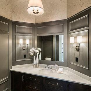 Aménagement d'un très grand WC et toilettes montagne avec un placard à porte shaker, des portes de placard en bois sombre, un WC séparé, un mur gris, un sol en bois brun, un lavabo encastré, un plan de toilette en surface solide, un sol marron et un plan de toilette blanc.
