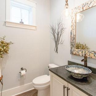 Cette image montre un WC et toilettes rustique de taille moyenne avec un placard avec porte à panneau surélevé, des portes de placard blanches, un WC séparé, un mur gris, un sol en bois foncé, une vasque, un plan de toilette en stéatite, un sol marron et un plan de toilette noir.