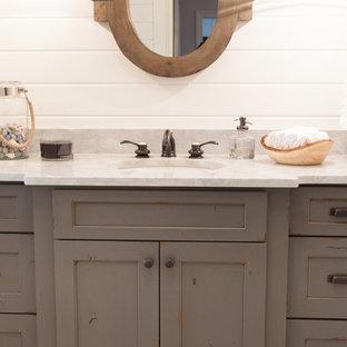 На фото: маленький туалет в стиле кантри с врезной раковиной, искусственно-состаренными фасадами, мраморной столешницей, раздельным унитазом, белыми стенами, фасадами с декоративным кантом, серой плиткой и белой плиткой с