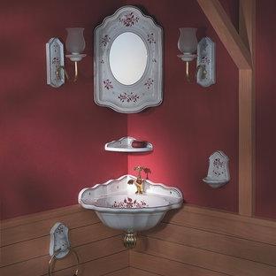 Foto på ett litet lantligt toalett, med ett väggmonterat handfat och röda väggar