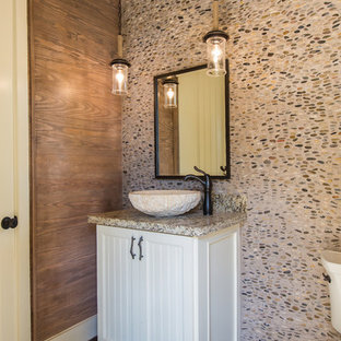 Medium sized rustic cloakroom in Houston with louvered cabinets, white cabinets, a one-piece toilet, multi-coloured tiles, pebble tiles, brown walls, dark hardwood flooring, a vessel sink, granite worktops and brown floors.