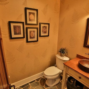 Photo of a medium sized rustic cloakroom in Other with freestanding cabinets, white cabinets, a two-piece toilet, brown walls, slate flooring, a built-in sink, wooden worktops and multi-coloured floors.