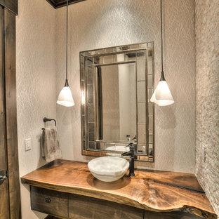 Cette image montre un WC et toilettes chalet de taille moyenne avec un placard à porte plane, des portes de placard en bois sombre, un carrelage beige, un carrelage de pierre, un mur beige, un sol en bois brun, une vasque, un plan de toilette en bois et un plan de toilette marron.
