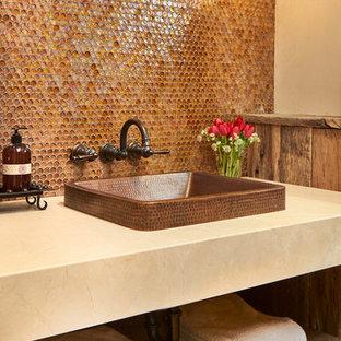 Urige Gästetoilette mit hellbraunen Holzschränken, Glasfliesen, beiger Wandfarbe, braunen Fliesen und beiger Waschtischplatte in Denver