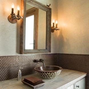 Cette photo montre un WC et toilettes sud-ouest américain avec un placard en trompe-l'oeil, un carrelage marron, un mur beige, une vasque, un plan de toilette en bois et un plan de toilette beige.