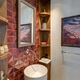 Foto på ett litet rustikt toalett, med släta luckor, skåp i mellenmörkt trä, röd kakel, beige väggar, mellanmörkt trägolv och ett piedestal handfat