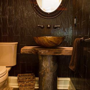 ニューヨークのラスティックスタイルのおしゃれなトイレ・洗面所 (ベッセル式洗面器、ヴィンテージ仕上げキャビネット、木製洗面台、一体型トイレ、茶色いタイル、ガラスタイル、茶色い壁、ブラウンの洗面カウンター) の写真
