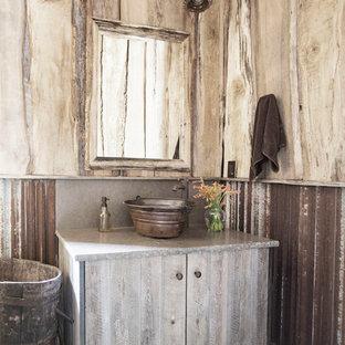 На фото: туалет в стиле рустика с искусственно-состаренными фасадами, настольной раковиной и разноцветным полом с