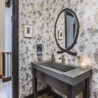 Photo of a country powder room in Tampa with grey cabinets, multi-coloured walls, light hardwood floors, an integrated sink, beige floor and grey benchtops.