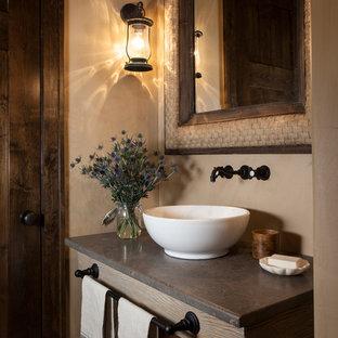 Exempel på ett rustikt toalett, med beige väggar och ett fristående handfat