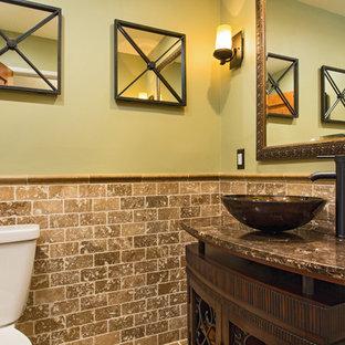 Foto di un piccolo bagno di servizio american style con consolle stile comò, ante in legno bruno, WC a due pezzi, piastrelle beige, piastrelle in travertino, pareti verdi, pavimento in travertino, lavabo a bacinella, top in granito e pavimento marrone