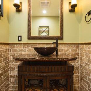 Пример оригинального дизайна интерьера: маленький туалет в стиле фьюжн с фасадами островного типа, темными деревянными фасадами, раздельным унитазом, бежевой плиткой, плиткой из травертина, зелеными стенами, полом из травертина, настольной раковиной, столешницей из гранита и коричневым полом