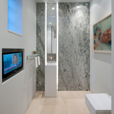 Powder room - modern gray tile marble floor powder room idea in DC Metro with a wall-mount toilet, gray walls and an integrated sink