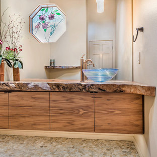 This is an example of a medium sized rustic cloakroom in San Francisco with flat-panel cabinets, medium wood cabinets, multi-coloured tiles, beige walls, pebble tile flooring, a vessel sink and wooden worktops.