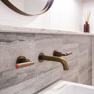 Неиссякаемый источник вдохновения для домашнего уюта: большой туалет в стиле современная классика с унитазом-моноблоком, серой плиткой, плиткой из травертина, серыми стенами, полом из керамогранита, подвесной раковиной, мраморной столешницей, белым полом и серой столешницей