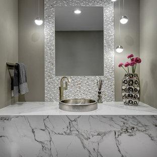 Cette image montre un WC et toilettes design de taille moyenne avec un mur gris, une vasque, un sol gris, un sol en bois foncé et un plan de toilette blanc.