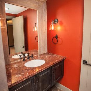 Idee per un bagno di servizio chic di medie dimensioni con ante con bugna sagomata, ante in legno bruno, WC monopezzo, piastrelle marroni, piastrelle in gres porcellanato, pareti rosse, pavimento in gres porcellanato, lavabo sottopiano, top in onice e pavimento marrone