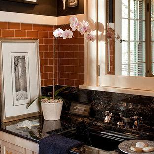 Idée de décoration pour un WC et toilettes craftsman avec un lavabo encastré, un placard avec porte à panneau encastré, des portes de placard blanches, un carrelage orange, un carrelage métro et un mur noir.