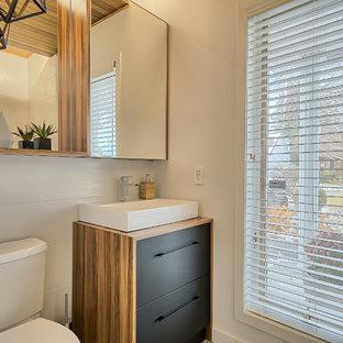 На фото: маленький туалет в стиле модернизм с плоскими фасадами, черными фасадами, унитазом-моноблоком, белой плиткой, керамогранитной плиткой, белыми стенами, полом из керамогранита, настольной раковиной и столешницей из ламината с