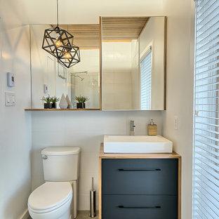 Свежая идея для дизайна: маленький туалет в стиле модернизм с плоскими фасадами, черными фасадами, унитазом-моноблоком, белой плиткой, керамогранитной плиткой, белыми стенами, полом из керамогранита, настольной раковиной и столешницей из ламината - отличное фото интерьера