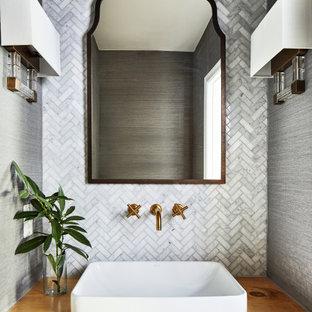 Cette image montre un petit WC et toilettes marin avec un placard sans porte, des portes de placard en bois clair, un WC séparé, un carrelage gris, un carrelage de pierre, un mur gris, un sol en bois foncé, une vasque, un plan de toilette en bois, un sol marron, un plan de toilette marron, meuble-lavabo suspendu et du papier peint.