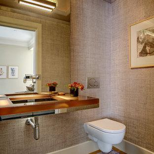 Cette photo montre un petit WC et toilettes tendance avec un placard à porte vitrée, un WC suspendu, un mur rose, un sol en bois clair, un lavabo suspendu, un plan de toilette en verre et un sol beige.