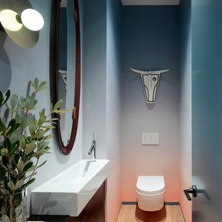 Cette image montre un WC et toilettes design avec un placard à porte plane, des portes de placard noires, un WC suspendu, un mur multicolore, un sol en bois brun, un plan vasque et un sol marron.
